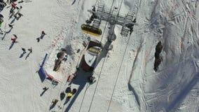 Krzesła dźwignięcie przy ośrodkiem narciarskim na zimnej pogodzie i jasnym widok z lotu ptaka ski park Narciarki i snowboarders w zdjęcie wideo