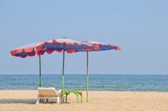 Krzesła i parasol na pięknej tropikalnej plaży z niebieskim niebem Obrazy Stock