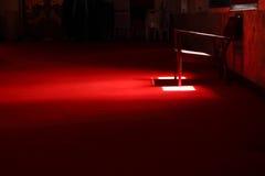 Krzesło w zmroku na czerwonym chodniku Zdjęcia Royalty Free