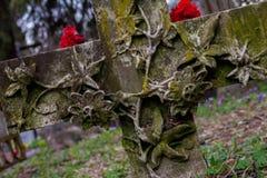 Krzyż przy cmentarzem z kwiatami zdjęcie stock