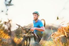 Krzyża członka turniejowego mężczyzna halny rowerzysta niesie jego rower up na wzgórze wierzchołku zdjęcia royalty free