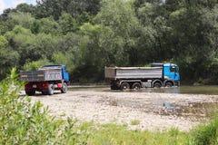 Krzyżować przez płytkiej halnej rzeki ciężarówki Transport towary w zasięg miejscach i niebezpiecznych warunkach ecol obraz stock