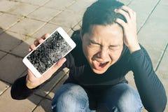 Krzycząca kobieta trzyma ekranu pęknięcie smartphone zdjęcie royalty free