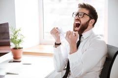 Krzyczący gniewny biznesmena obsiadanie w biurze zdjęcie stock