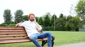 Krzyczący gniewny mężczyzna uczęszcza rozmowę telefonicza w parku, czerwonej brodzie i hairs, zbiory