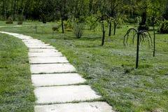 Krzywa ścieżka betonowe płytki na słonecznym dniu Park z długą drogą wzdłuż drzew Park z długą drogą wzdłuż drzew Fotografia Royalty Free