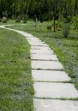 Krzywa ścieżka betonowe płytki na słonecznym dniu Park z długą drogą wzdłuż drzew Park z długą drogą wzdłuż drzew T Obraz Royalty Free