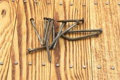 Krzywy ośniedziali gwoździe na drewnianym tle Zdjęcie Stock
