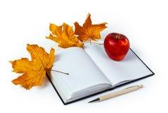 Książka, ballpen, jabłczani i żółci liście klonowi, Na biały tle Fotografia Stock