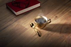 Książka i eyeglasses zbliżamy złotą filiżankę kawy Obraz Stock