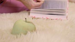 Książka i jabłko przy futerkowym dywanem zdjęcie wideo