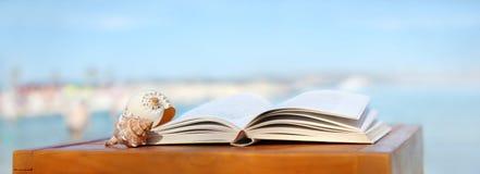 Książka i skorupy na wyrzucać na brzeg stół Obraz Royalty Free