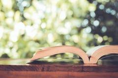 Książka na drewnianym stole z zamazanym tłem fotografia stock
