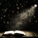 Książka przeciw blask księżyca nocy miastu zdjęcia stock