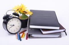 Książka z cykota rocznika zegarem, sztucznego kwiatu rośliną i kolorową kredką na bielu stole, Obraz Royalty Free