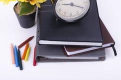 Książka z cykota rocznika zegarem, sztucznego kwiatu rośliną i kolorową kredką na bielu stole, Obrazy Stock