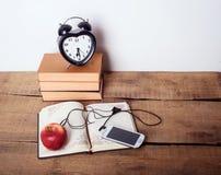 Książki, budzik, notepad, telefon komórkowy i jabłko na drewnianym tle, Obraz Royalty Free