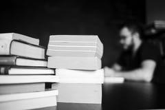 Książki i inżynier oprogramowania są siedzący i pracujący na tle Obraz Stock