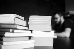 Książki i inżynier oprogramowania są siedzący i pracujący na tle Fotografia Stock