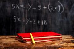Książki i kreda blackboard z równaniem Fotografia Royalty Free