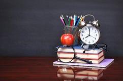 Książki, jabłko, budzik i ołówki na drewnianym biurko stole, Zdjęcia Royalty Free