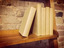 Książki na drewnianej półce blisko ściana z cegieł Obraz Royalty Free