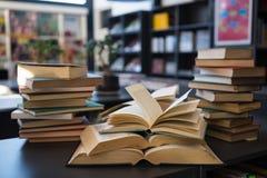 Książki na stole przeciw półce w bibliotece przy szkołą zdjęcia stock
