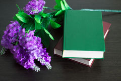 Książki z kwiatami na drewno stole Obrazy Stock