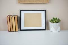 Książki z obrazek ramą i garnek rośliną Fotografia Stock