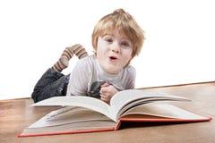książkowej chłopiec twarzy śmieszny ciągnięcia czytanie podczas gdy Zdjęcie Stock