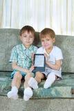 książkowych chłopiec elektroniczny czytanie dwa Zdjęcia Royalty Free