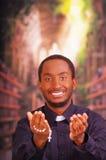 Ksiądz katolicki jest ubranym tradycyjną klerykalnego kołnierza koszulową trwanie okładzinową kamerę, mienie ręki out z różana kr Fotografia Stock