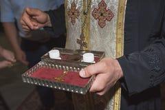 Ksiądz trzyma kościelnych naczynia, żołędzie, ceremonia wodny ochrzczenie, różnorodni przedmioty potrzebujący dla ochrzczenia chr Obrazy Stock