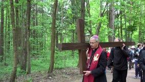 Ksiądz w soutane i stary popielaty kierowniczy mężczyzna niesiemy krzyż jak jezus chrystus zdjęcie wideo