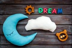 Księżyc poduszka, chmury, sen kopia i zabawki dla stawiającego dziecka w łóżku na drewnianego tła odgórnym widoku, fotografia stock