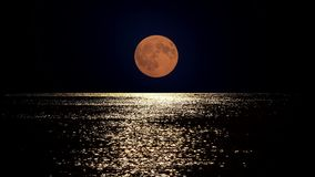 Księżyc w pełni światło odbija w wodzie morskiej, lato romantyczna noc przy nadmorski zbiory