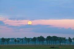 Księżyc w pełni nad łąkami przy wschodem słońca Obraz Stock