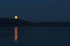 Księżyc w pełni wzrasta nad niektóre wzgórzami na jeziorze, doskonale odbija Fotografia Stock