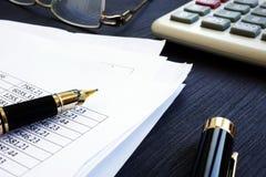 księgowość Pieniężny raport z postaciami i kalkulatorem na biurku obraz stock