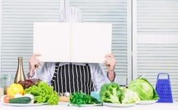 Ksi??kowa przepis kopii przestrze? Obs?uguje szefa kuchni w kapeluszu i fartuch czytaj?cej ksi??ce E r zdjęcia stock