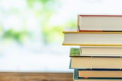 Ksi??kowa sterta w bibliotecznym pokoju na tabela i zamazanych drzewach na ulicie z powrotem szko?y poj?cie zdjęcie royalty free