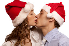 Kssing couple in Christmas hats Stock Images