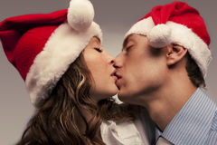 Kssing couple in Christmas hats Royalty Free Stock Photos