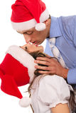 Kssing couple in Christmas hats Royalty Free Stock Photography