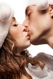 Kssing couple in Christmas hats Royalty Free Stock Image