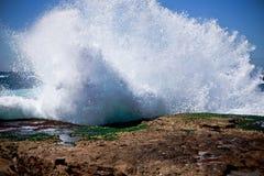 Küstenunterbrecherwelle, die Felsen spritzt Stockfotografie