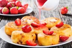 Köstliche Hüttenkäsepfannkuchen mit Rosinen und Erdbeeren Stockfotografie