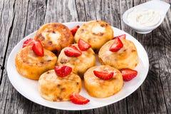 Köstliche Hüttenkäsepfannkuchen mit Rosinen und Erdbeeren Stockbilder