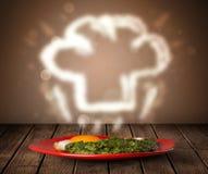 Köstliche Lebensmittelplatte mit Chefkochhut Stockfotos