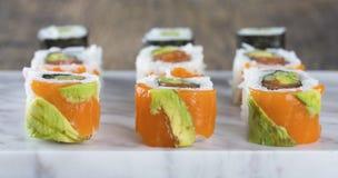 Köstliche Mischsushi vereinbarten auf weißer Marmoroberfläche Stockfotografie